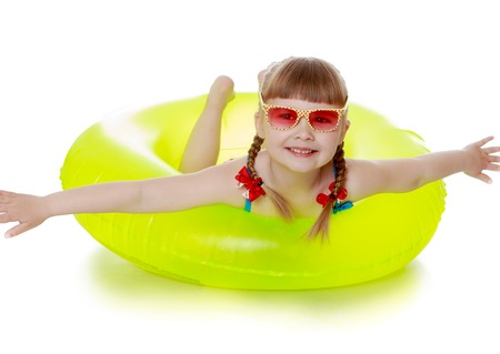 vacationing: The little blonde girl in the pink glasses. The girl is in a swimsuit on a yellow rubber ring for swimming, spreading their arms . The girl is vacationing with his parents in the seaside resort-Isolated on white background