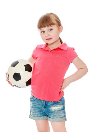 beautiful bangs: Beautiful little blonde girl with short bangs and long braids on his head. The girl is dressed in a red top and short denim shorts . In the hand of a girl holding a soccer ball , close-up-Isolated on white background