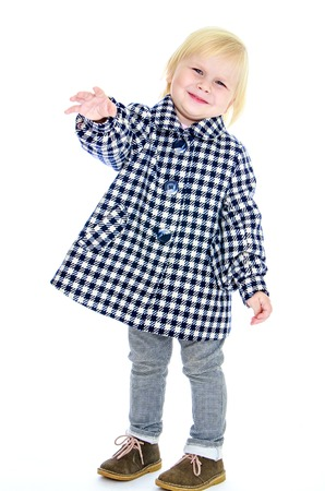 short wave: Funny little blonde girl with short hair to wave his arms. A girl wearing a plaid coat and gray jeans-Isolated on white background