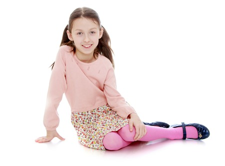 petite fille avec robe: Belle maigre petite fille avec de longs cheveux tressés en nattes est assis sur le sol. -Isolated Sur fond blanc