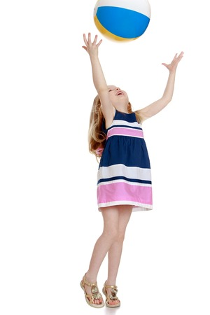 Cheerful little girl in a short summer dress playing with a ball . The girl throws the ball with his hands up-Isolated on white background