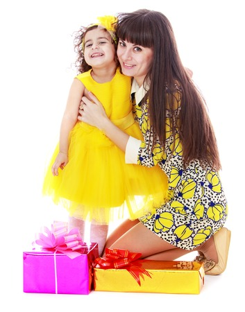 decorate: Fun little curly-haired girl in bright yellow dress and a yellow band on his head, hands hugging his beloved young mother. Mom stands in front of the girl on her knees , lay the box Packed with beautiful Christmas gifts-Isolated on white background Stock Photo