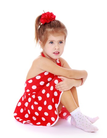 hugging legs: very beautiful little girl with a red bow on her head. The girl dressed in red, summer, short polka dot dress. Girl sitting on the floor in white socks hugging her legs turned sideways to the camera-Isolated on white background