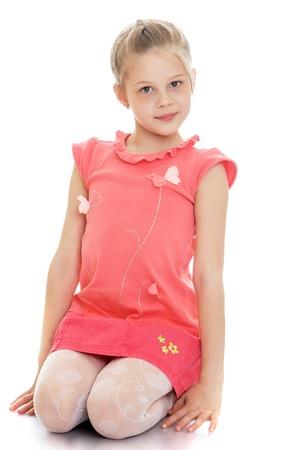 Cute blanke meisje in een rode blouse en een korte roze rok zit op je schoot en kijken naar de camera geïsoleerd op een witte achtergrond