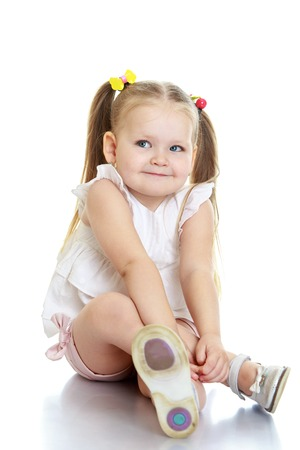 hugging legs: Funny little round-faced girl with pigtails on the head to sit on the floor hugging her legs -Isolated on white background