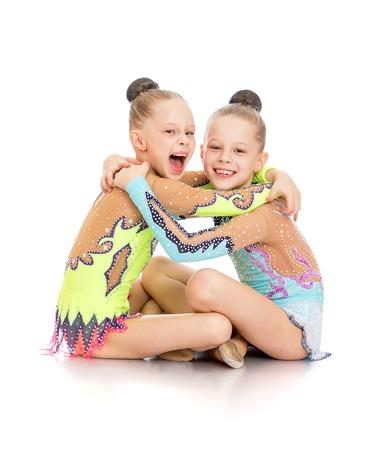 gimnasia ritmica: Riendo gimnastas niñas sentados en el piso abrazos y divertido aislado contra el fondo blanco
