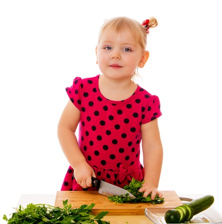 girl with knife: The little blonde girl in a red polka dot dress cut with a real knife on the kitchen blackboard vegetables . The girl helps her mother to do the salad-Isolated on white background