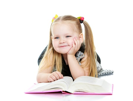 Beautiful little chubby girl long blonde braids on his head reading a book. The girl lies on the floor and dreams