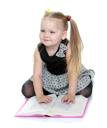 chubby girl: Beautiful little chubby girl sitting on the floor spread out in front of a book-Isolated on white background