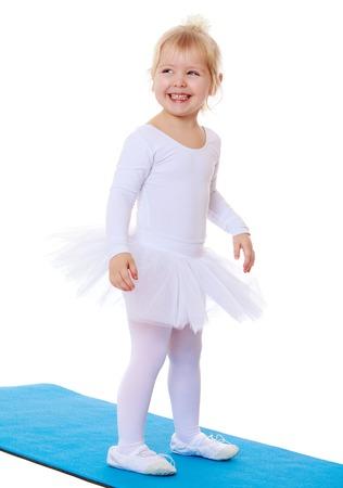 turnanzug: Nettes kleines blondes Mädchen im weißen Gymnastik Turnanzug steht auf der Matte und lächelt-Isoliert auf weißem Hintergrund Lizenzfreie Bilder