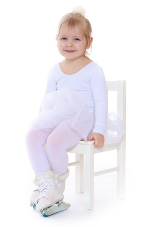 little blonde girl: Cute little blonde girl in a white suit for figure skating sit on the Mat and smiles. At the feet of the girls are dressed skates for figure skating-Isolated on white background