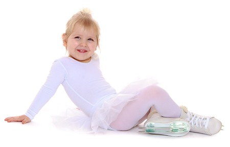 Cute little blonde girl in a white suit for figure skating sits on the floor and smiles. At the feet of the girls are dressed skates for figure skating-Isolated on white background 免版税图像
