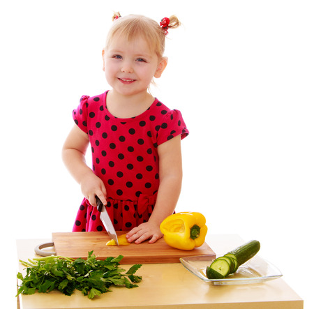ponytails: Positive little blonde girl with small ponytails on my head cuts on a wooden Board with a knife peppers. The girl helps her mother to cook salad-Isolated on white background Stock Photo