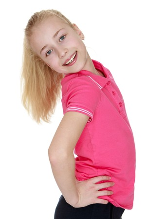 broadside: Beautiful girl of school age in the red shirt and short black shorts stands broadside to the camera. Long girls hair braided in a ponytail. Stock Photo