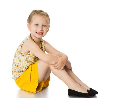 short shorts: Stylish trendy blonde girl.The girl is dressed in a colorful silk blouse with short sleeves and yellow short shorts. Girl sitting on the floor clutching her leg-Isolated on white background