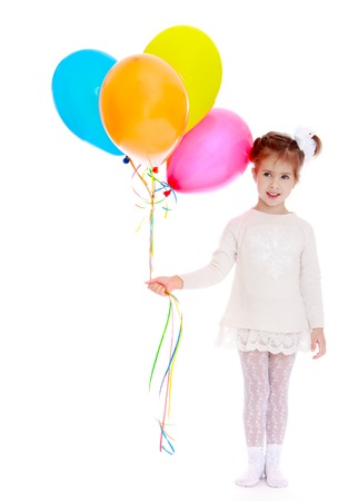 white party: Adorable little girl with a ponytail tied with a white bow on her head holding a bunch of colourful balloons. The girl dressed in a short white dress and white tights-Isolated on white background