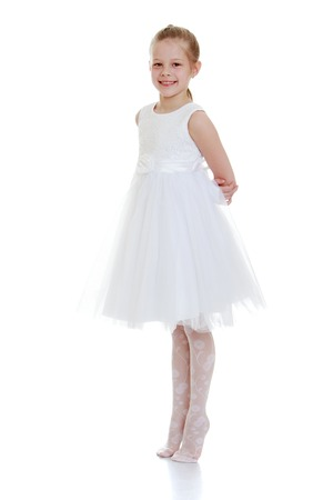 very beautiful little girl in a long white ballet dress with his hands behind his back standing on toes-Isolated on white background 免版税图像