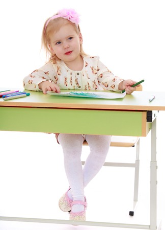 gray eyes: Adorable little blonde girl with gray eyes draws markers sitting at the Desk-Isolated on white background