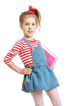 fille pull: Adorable petite fille aux yeux gris avec des cheveux longs attach�s avec un ruban rouge. La jeune fille est v�tue d'une jupe en jean et un pull ray� court. Fille tenant sous son bras un livre �pais. Gros plan-Isol� sur fond blanc