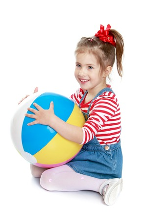 denim skirt: Adorable little grey-eyed girl with long hair tied with a red bow. The girl is dressed in a short denim skirt and striped sweater. Girl sitting on the floor and hugging a large beach striped ball . -Isolated on white background
