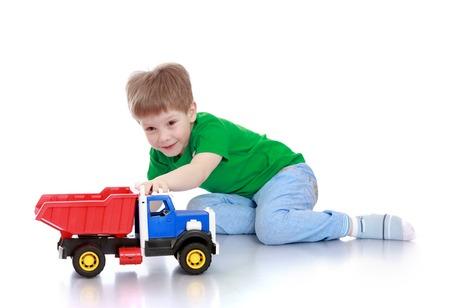 Grappige kleine bruin-eyed jongen zittend op de vloer en spelen met de machine-geïsoleerd op een witte achtergrond Stockfoto