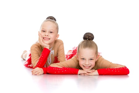 brown  eyed: Beautiful slender brown eyed girls gymnast lie on the floor and looking at the camera-Isolated on white background