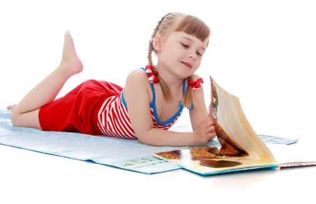 Adorable little girl lies and sunbathes on a towel. The girl is dressed in a striped bathing suit . She reads the book-Isolated on white background Stock Photo
