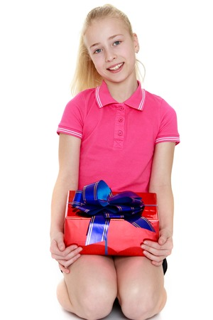 gray eyes: Beautiful blond girl with gray eyes holding on her knees a box tied with a bow. The girl wearing the pink Jersey with short sleeves and short black shorts-Isolated on white background