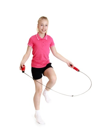Beautiful blond girl with gray eyes jumping rope. The girl wearing the pink Jersey with short sleeves and short black shorts-Isolated on white background