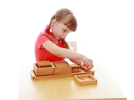 Mooi weinig blonde meisje met kort pony en grijze ogen zitten aan de tafel in het Montessori milieu en doet wiskunde