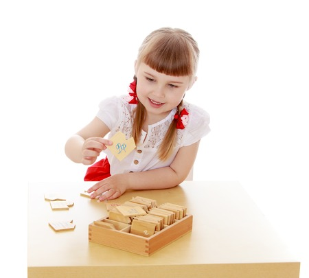 montessori: Beautiful little blonde girl with short bangs and grey eyes sitting at the table in the Montessori environment-Isolated on white background Stock Photo