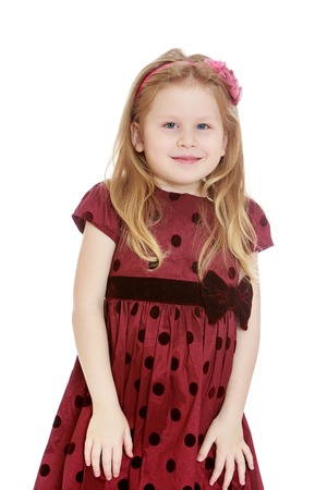 gray eyes: Beautiful little girl with flowing blond hair and gray eyes posing for the camera. On the head the girl has a pink bezel, a girl dressed in a beautiful brown polka dot dress,she put her hands on her knees-Isolated on white background