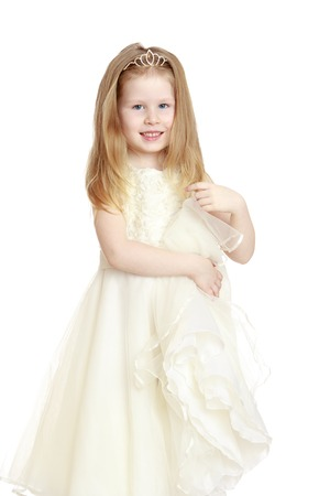 gray eyes: Cute little girl with gray eyes and blond hair in a long white Princess dress . Girl holding the edge of the dress by hand . Closeup-Isolated on white background Stock Photo