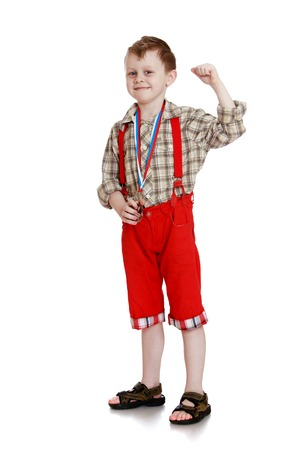 red shorts: Joyful grey-eyed,fair-haired boy in a long red shorts with straps and a plaid shirt. on the neck of the boy on the ribbons hanging sports medals.-Isolated on white background