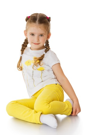 summer wear: Beautiful little green-eyed girl with blond hair braided in pigtails. Girl sitting on the floor crooking his feet under him in a white t-shirt with picture and yellow jeans-Isolated on white background