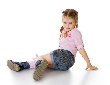 little girl dress: Pretty little green-eyed girl with blond hair braided in pigtails. Girl sitting on the floor crooking his feet under him in a pink t-shirt and short denim shorts-Isolated on white background Stock Photo
