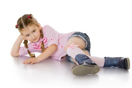 Niña bonita de ojos verdes con el pelo rubio trenzado en trenzas. La niña se encuentra en el suelo doblando sus pies debajo de él en una camiseta rosa y pantalones cortos de mezclilla corto-Aislado en el fondo blanco