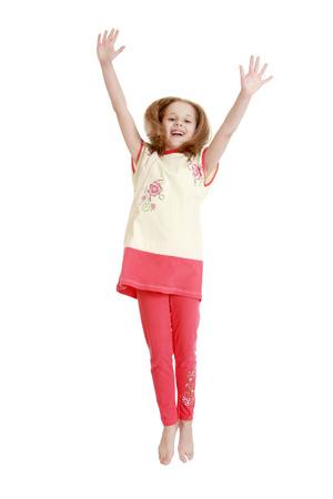 gente saltando: Ni�a alegre en un traje pantal�n rojo salta levantaron sus brazos-alta Aislado en el fondo blanco Foto de archivo