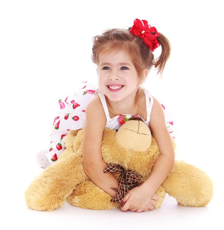 playing with spoon: Happy little girl with a short ponytail on the head in which braided red bow, playing with a Teddy bear lying on the floor-Isolated on white background