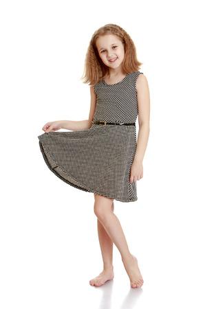 Skinny jong meisje staat op blote voeten in een grijze zijde korte jurk-Geïsoleerd op witte achtergrond Stockfoto