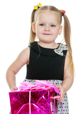 Cute little round-faced girl with long tails on the head that hold the rubber bands. The girl is dressed in a festive dress she holds in her hands a gift Stock Photo
