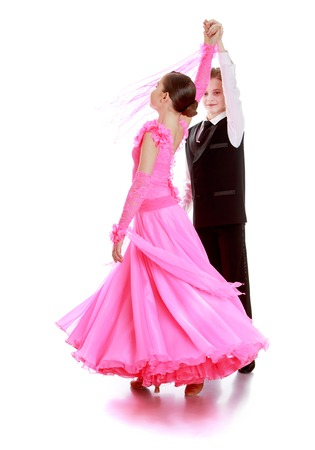 cha: Boy and girl of school age are engaged in ballroom dancing. The boy is dressed in a simple three girl with magnificent long pink dress. Steam swirls-Isolated on white background