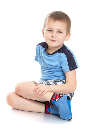 young boy: Cheerful little boy meadow t-shirt and shorts is sitting on the floor cross-legged-Isolated on white background
