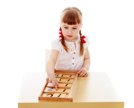 little girl with short bangs and thin hair on his head sitting at a table in a Montessori kindergarten. A girl student of mathematics-Isolated on white background Imagens