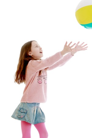 denim skirt: Cute skinny girls of school age in a very short denim skirt and a pink sweater throws hands the ball-Isolated on white background