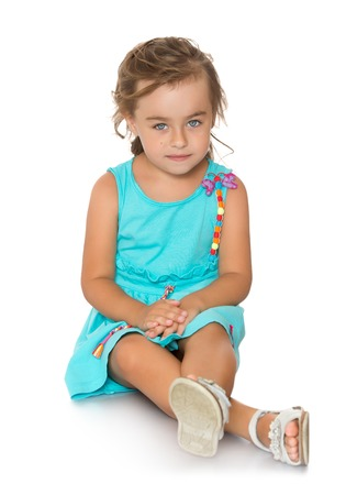 legs folded: Pretty little girl in a blue summer dress sits on the floor with legs folded crosswise-Isolated on white background