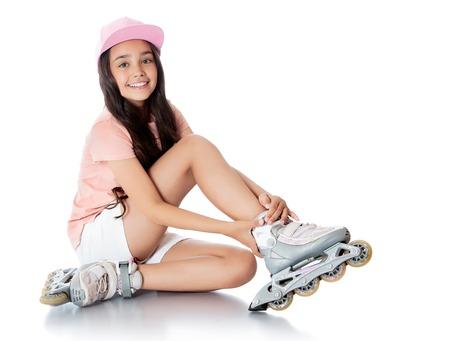 patín: Encanto niña de cabello oscuro en edad escolar en pantalones cortos blancos cortos y una camiseta rosa sentada en el suelo y trata de patines pie. -Aisladas sobre fondo blanco