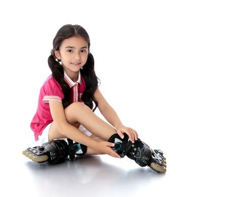 rollerblading: Encanto niña de cabello oscuro en edad preescolar en pantalones cortos blancos cortos y una camiseta rosada que se sienta en el suelo y trata de patines pie. -Aisladas sobre fondo blanco