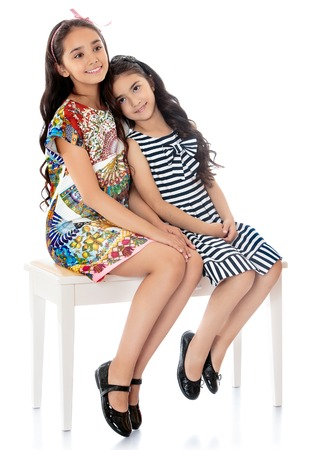 Beautiful girls sisters dressed in short summer dresses sitting on the couch-Isolated on white background