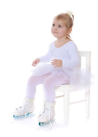 on the skids: Cute little skater girl sat down on the chair. On the feet white girls skates on two skids , the girl just started to learn figure skating-Isolated on white background Stock Photo